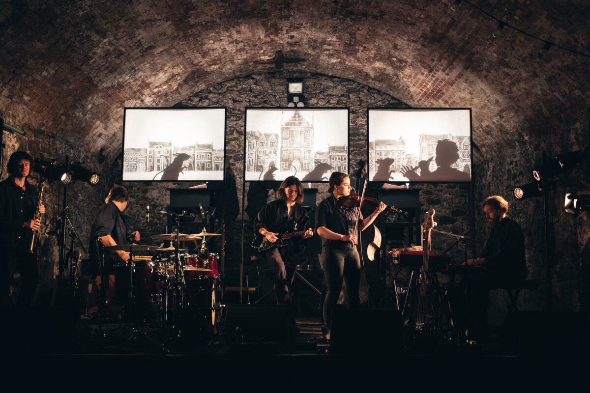 Band performing in tunnel with images